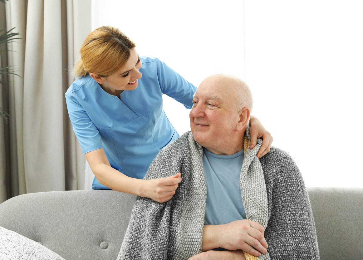 caregiver smiling at the senior man