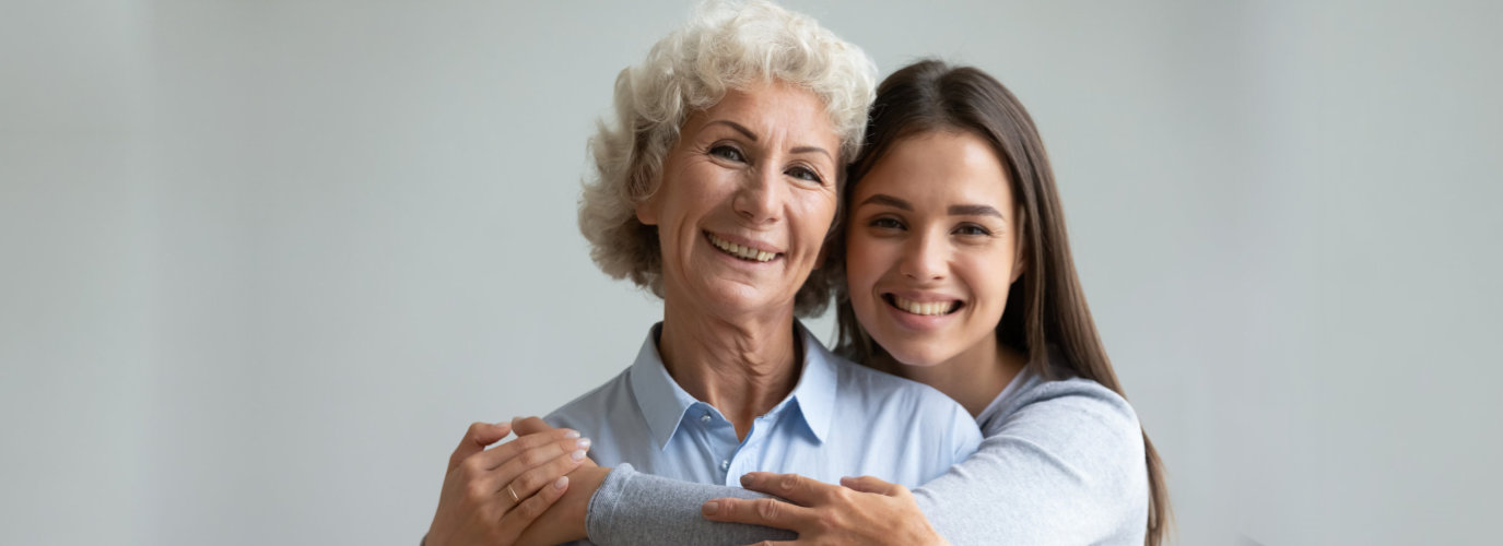 caregiver hugging senior woman indoor