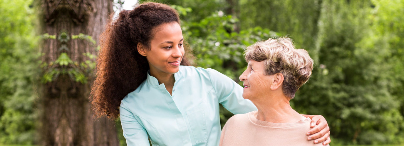 female caregiver and senior woman smiling outdoor